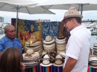 Hopeful street vendor with a hat customer